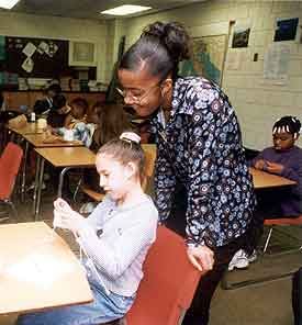 photo of student helping another student, who is knitting